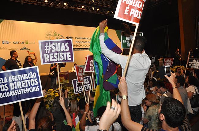 Foto mostra leitura do Regimento Interno interrompida. Centenas de placas com palavras de ordem em defesa dos direitos sociais foram levantadas