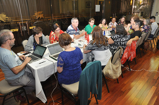 Imagem mostra a comissão organizadora da Conferência, reunida em volta de uma mesa.