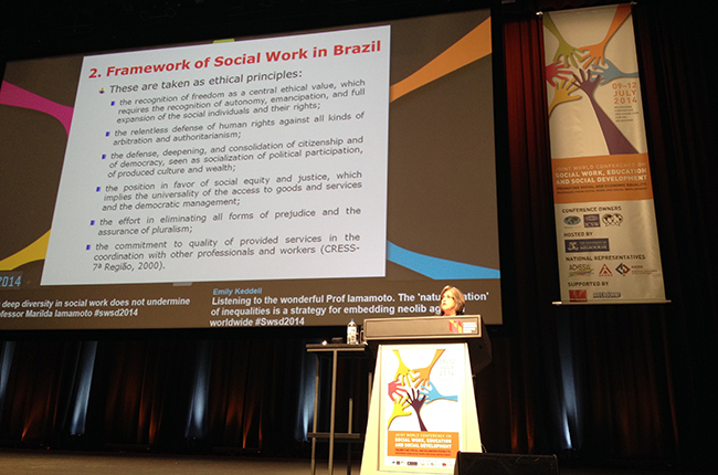 Imagem mostra professora Marilda Iamamoto palestrando durante Conferência Mundial