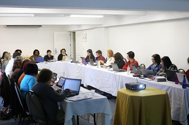 Foto mostra as conselheiras do CFESS e as assessorias sentadas em uma mesa em forma da letra U, debatendo sobre os eventos do CFESS