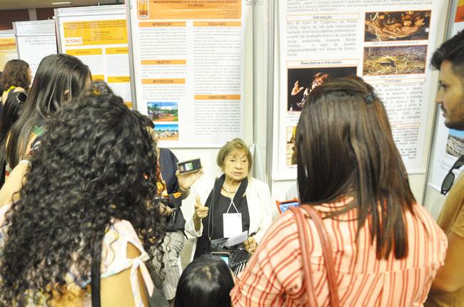 Imagem mostra professora Joaquina Barata falando de sua pesquisa para participantes do evento.