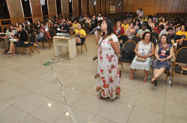 Imagem da apresentação do eixo administrativo-financeiro, durante a fala da primeira-tesoureira do CFESS, Cheila Queiroz, à frente.