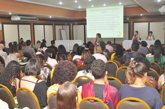 Imagem mostra participantes reunidos no eixo da Formação Profissional, durante a fala da conselheira do CFESS Daniela Neves à frente.