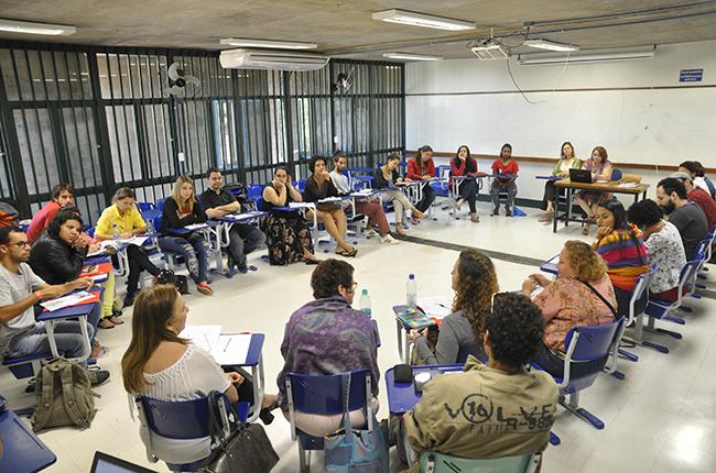 Foto mostra assistentes sociais e estudantes de Serviço Social debatendo em sala