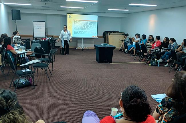 Imagem mostra sala onde ocorreu o curso. Ao fundo está a assessora jurídica do CFESS, Sylvia Terra, e os/as participantes sentados acompanhando a aula expositiva.