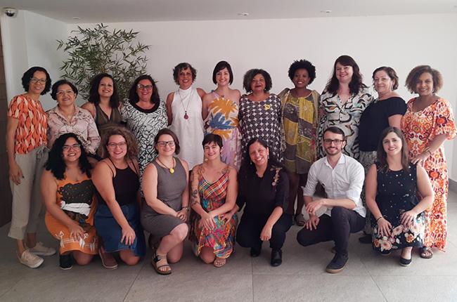 Imagem mostra foto das integrantes da nova gestão do CFESS, feita ainda durante a campanha. Na imagem, as novas diretoras e diretor estão abraçados em duas fileiras, em pé e agachadas.