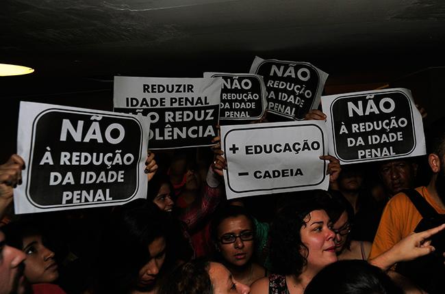 Imagem mostra manifestantes na Câmara segurando cartazes contrários à redução da idade penal para 16 anos