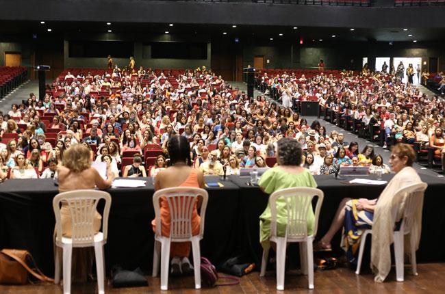 Imagem do alto do palco do auditório do centro de convenções mostra a mesa com palestrantes e o público ao fundo.