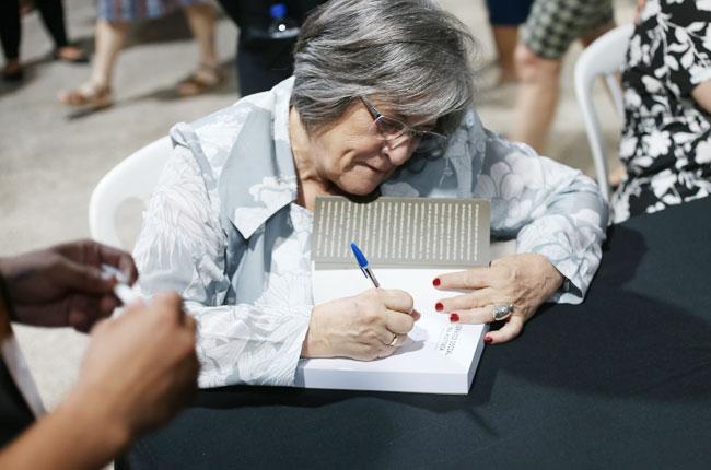 Professora Marilda Iamamoto autografa livro para participantes do evento.