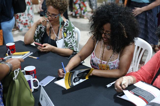 Imagem mostra autora autografando livros para participante do evento.