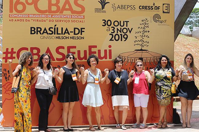 Imagem de assistentes sociais tirando foto no painel do CBAS, com a hashtag CBAS EU FUI.