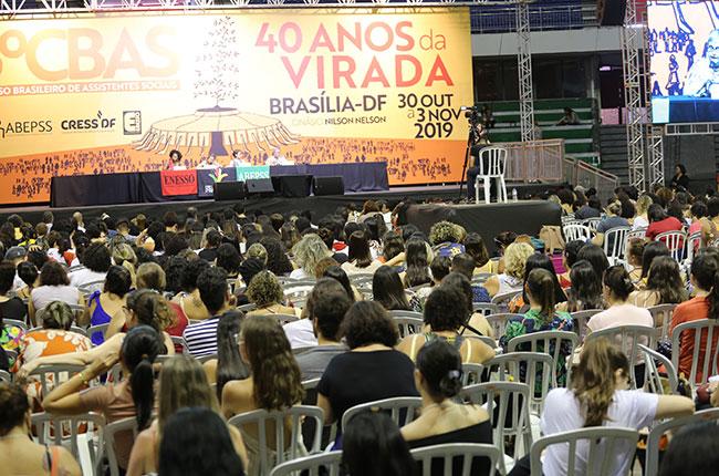 Imagem do público assistindo à mesa da tarde, com o palco e as palestrantes ao fundo.