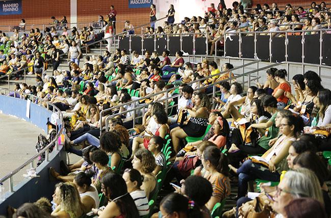 Imagem de participantes que assistiram da arquibancada do ginásio.