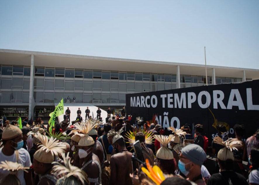 Imagem mostra povos indígenas mobilizados em frente ao Palácio do Planalto, em Brasília, com uma faixa com a mensagem: Marco Temporal Não.