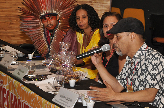 Imagem mostra palestrante Wilson Honório da Silva e outras pessoas na mesa de debates