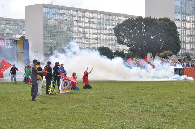 Imagem mostra manifestantes ajoelhados em meio ao gás lacrimogênio que tomou conta da Esplanada