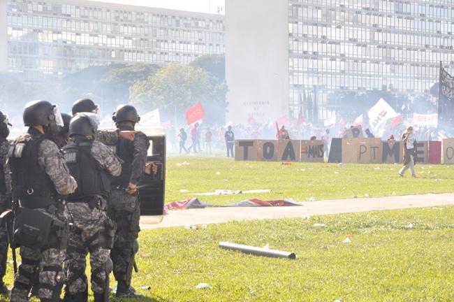 Foto mostra tropa de choque com escudos, cassetetes e armas que disparam bala de borracha
