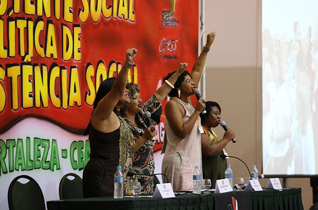 Imagem mostra as conselheiras negras do CFESS em pé, com os punhos erguidos, enquanto bradam palavras de ordem contra o racismo