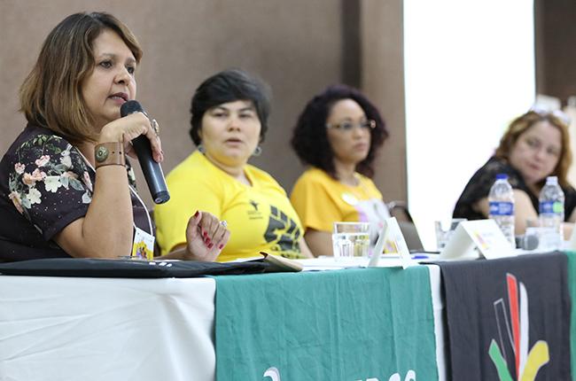 Fotografia da palestrante Erivã Velasco (UFMT) em destaque, com suas colegas de mesa ao fundo.