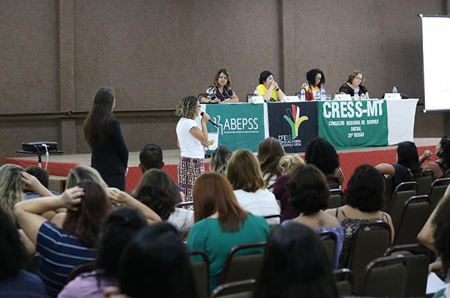 Imagem mostra assistente social em pé fazendo uma pergunta para as palestrantes da mesa, no momento de debate