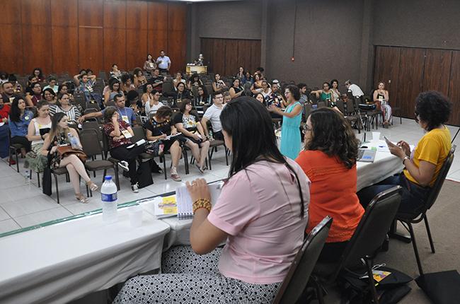 Imagem mostra oficina sobre o trabalho da categoria na Assistência Estudantil. As pessoas estão sentadas olhando para uma projeção.