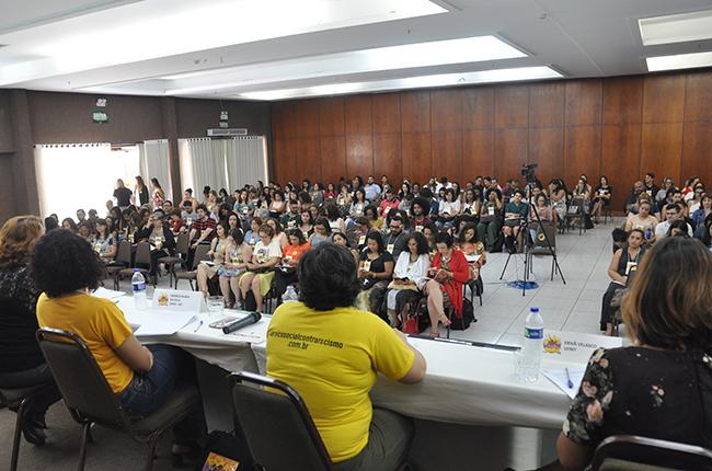 Fotografia tirada na perspectiva atrás das palestrantes mostra auditório cheio, com participantes acomodados/as nas cadeiras