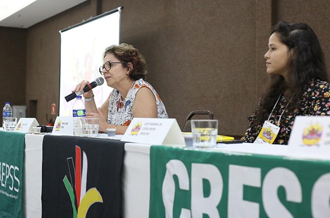 Imagem mostra fotografia da conselheira Tânia Diniz, falando na mesa de encerramento
