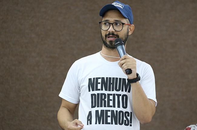 Imagem mostra o assistente social Fábio Santos (Sintufs) em pé, segurando microfone em sua fala. Ele está com uma camisa com os dizeres nenhum direito a menos