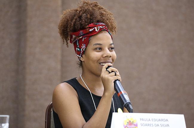 Fotografia mostra Paula Soares, estudante de Serviço Social da UFMT, falando para o público. Sua expressão é de alegria