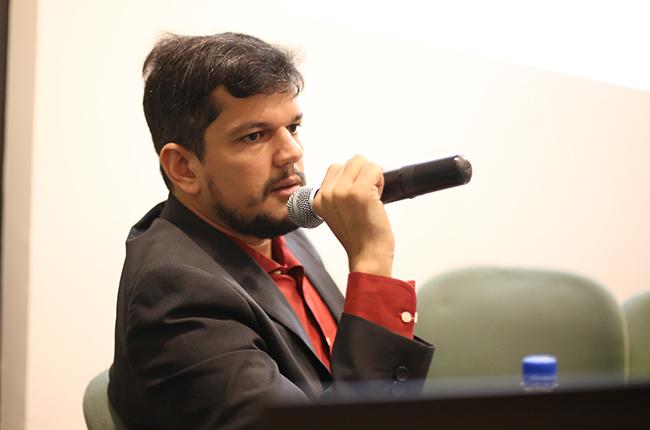Foto do palestrante Diego segurando o microfone na mesa de debate