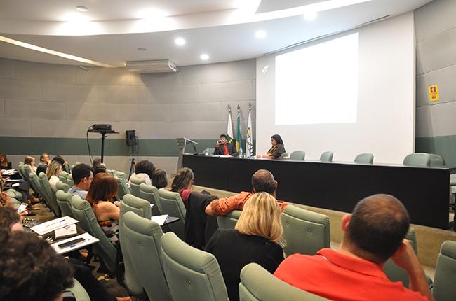 Foto do auditório com pessoas sentadas nas cadeiras e palestrantes