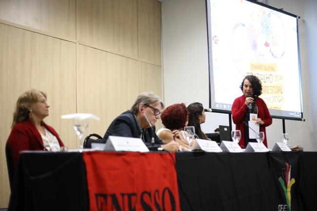 Imagem mostra a palestrante Rosa Prédes (Ufal) em destaque na mesa de debates, enquanto outros/as palestrantes acompanham sua fala