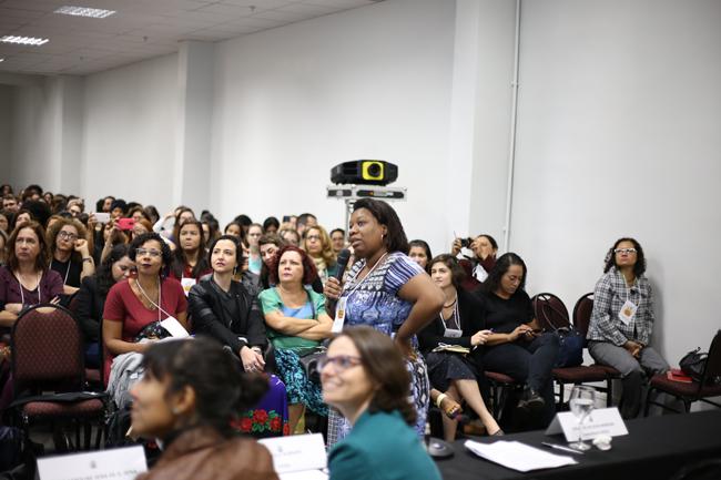 Imagem mostra a conselheira do CFESS Solange Moreira em pé apresentando para o auditório a pesquisa sobre as comunidades terapêuticas