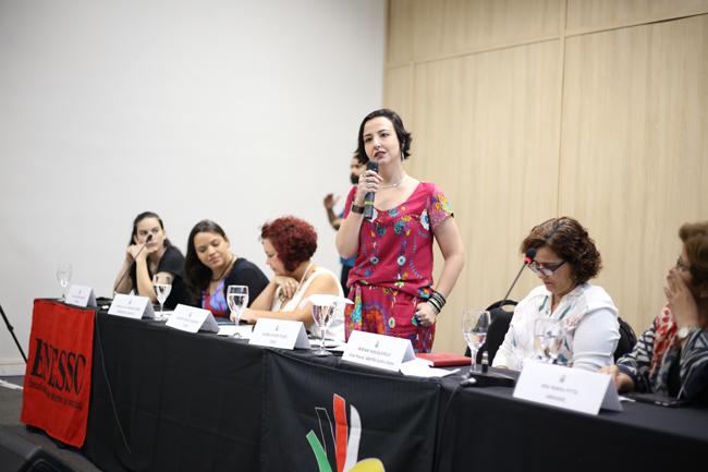 Imagem mostra participantes da mesa de abertura. Em destaque a conselheira do CFESS Elaine Pelaez com microfone na mão