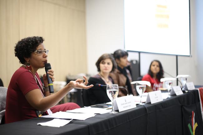 Imagem mostra a presidente do CFESS Josiane Soares apresentando sua palestra na mesa de debates
