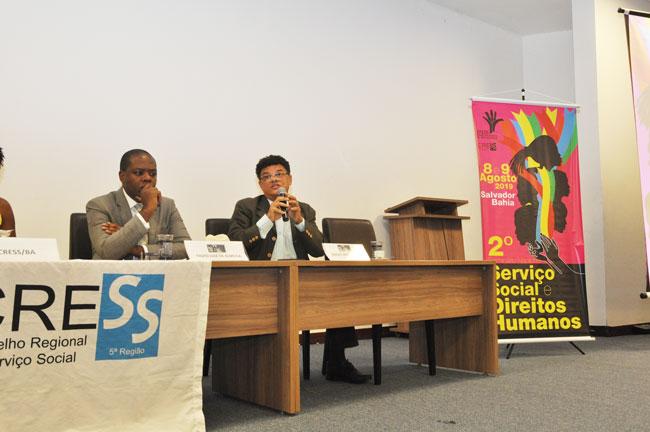 Imagem de dois advogados durante a primeira mesa de debate do seminário, no momento em que um deles está com a fala.