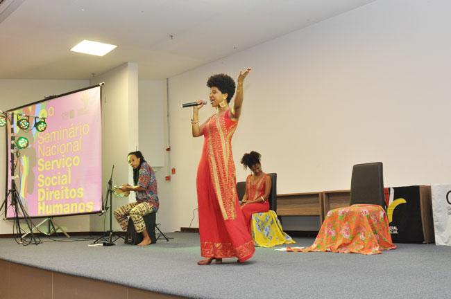 Imagem da atividade cultural ao fim do primeiro dia, com apresentação do Recital Vozes Negras, com três mulheres negras e dois músicos no palco.