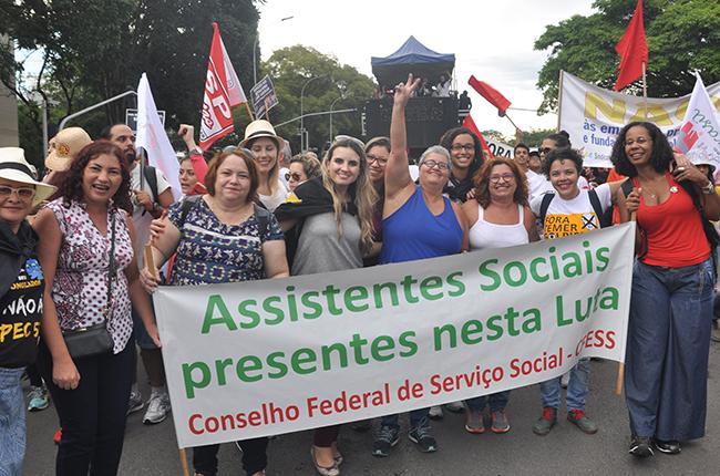 Foto mostra conselheiras do CFESS, assistentes sociais e professoras com a faixa 'assistentes sociais na luta'