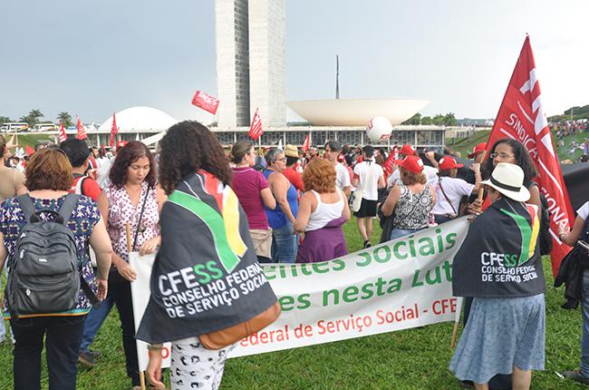 Foto mostra manifestantes se organizando em frente ao Congresso, com faixas, bandeiras etc.