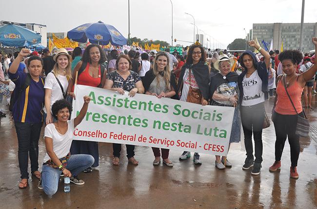 Foto mostra estudantes e profissionais com a faixa 'assistentes sociais na luta'