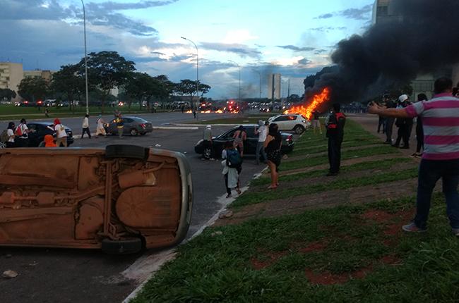 Foto mostra carro em chamas e outro virado. Protesto de manifestantes frente à violência da PM