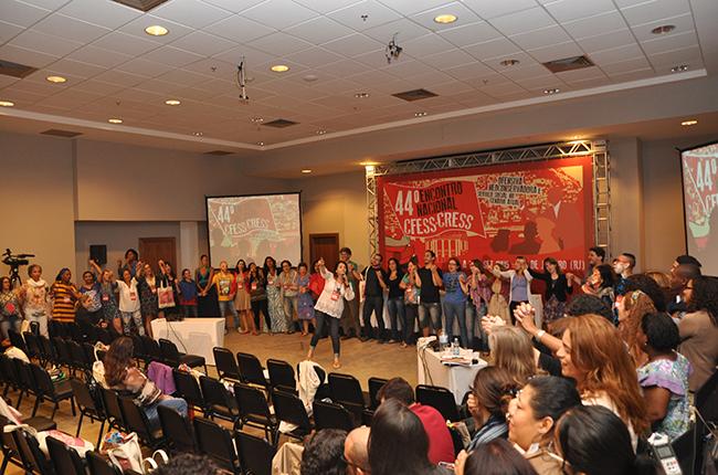 Imagem mostra assistentes sociais de mãos dadas, em círculo, cantando Pra não dizer que não falei de flores, de Geraldo Vandré