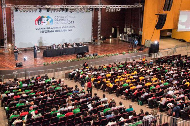 Imagem mostra auditório visto de cima e participantes da Conferência