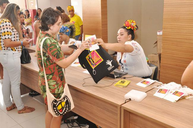 Imagem do credenciamento do evento, no momento em que uma recepcionista entrega o material a uma participante.