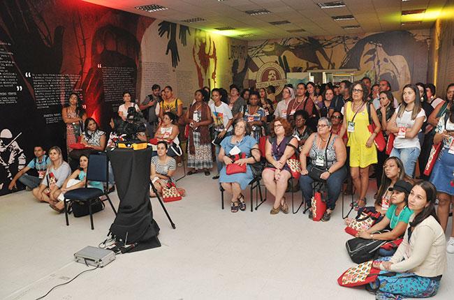 Imagem da professora Marilda Iamamoto assistindo ao vídeo da exposição