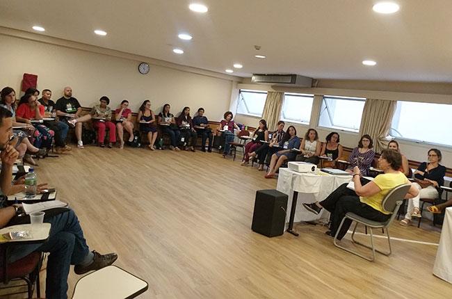 Imagem da turma em círculo, com a professora Lúcia Barroco no centro, durante o módulo.