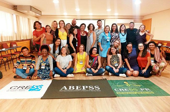 Imagem da turma do curso Ética em Movimento, em pé, reunida, com as bandeiras de CRESS e Abepss à frente.