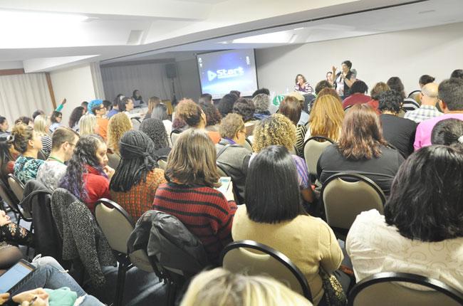 Imagem mostra a coordenadora da Comissão de Formação do CFESS, Daniela Neves, em pé, falando sobre as diretrizes do Fórum para os/as participantes