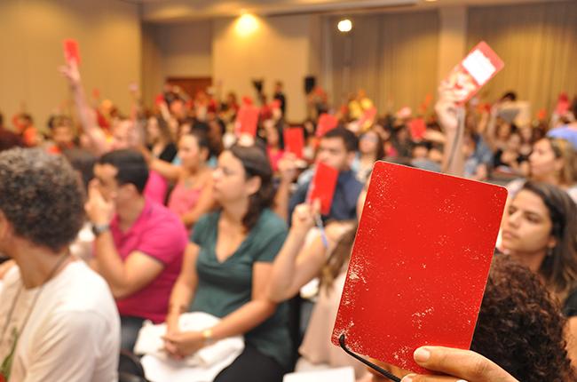 Imagem mostra assistente social levantando um crachá vermelho, de delegado(a), durante a votação na Plenária Final