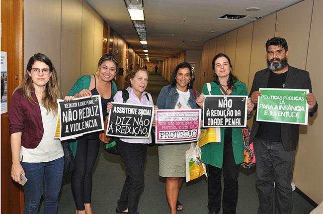 Imagem mostra integrantes da Frente contra a Redução da Maioridade Penal segurando cartazes nos corredores da  Câmara